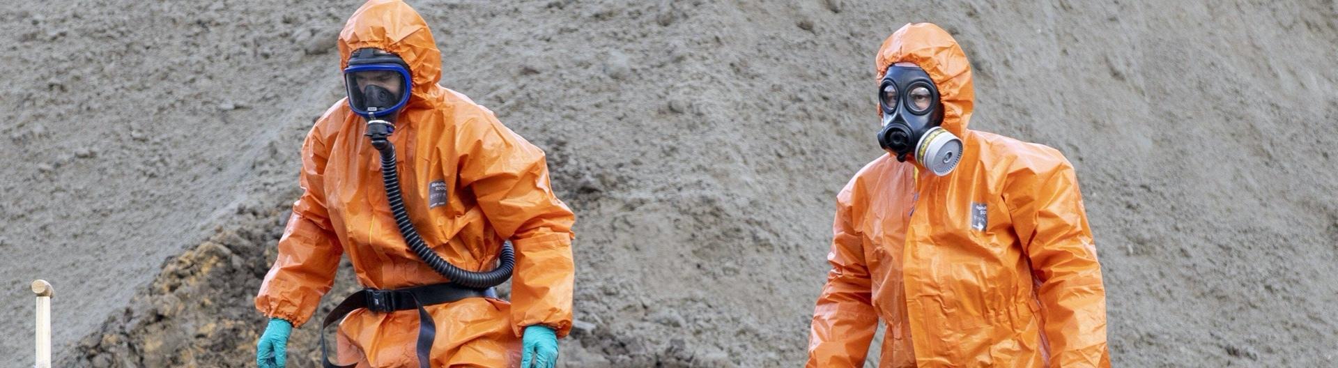 Zwei Männer in orangenem Schutzanzug