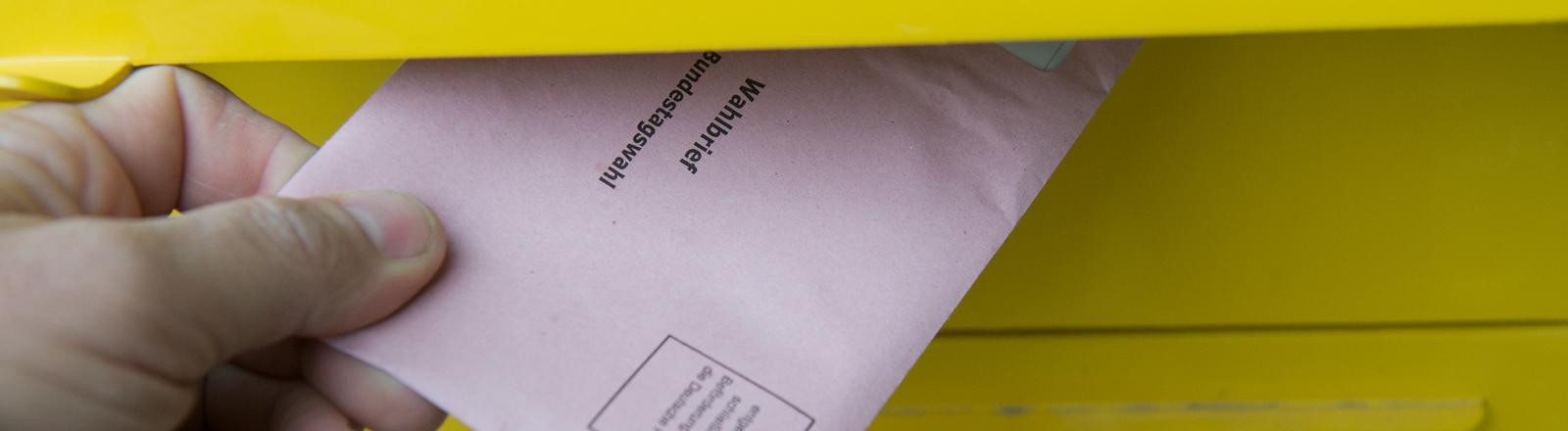 eine hand wirft einen stimmzettel in einen postkasten