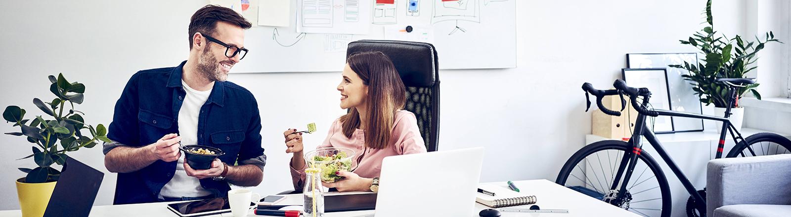 Zwei Menschen unterhalten sich beim Essen im Büro