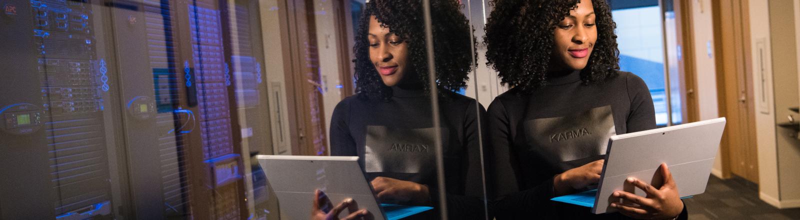 Eine Frau lehnt an einer Glaswand und hält ein Notebook in der Hand.