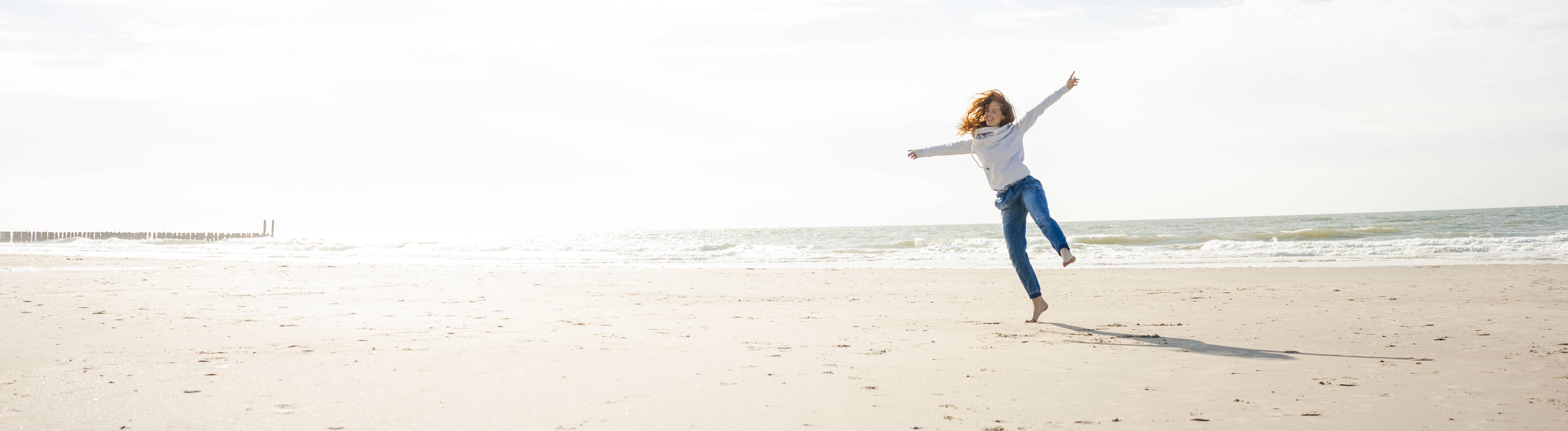 Frau tanzt allein am Strand und lacht