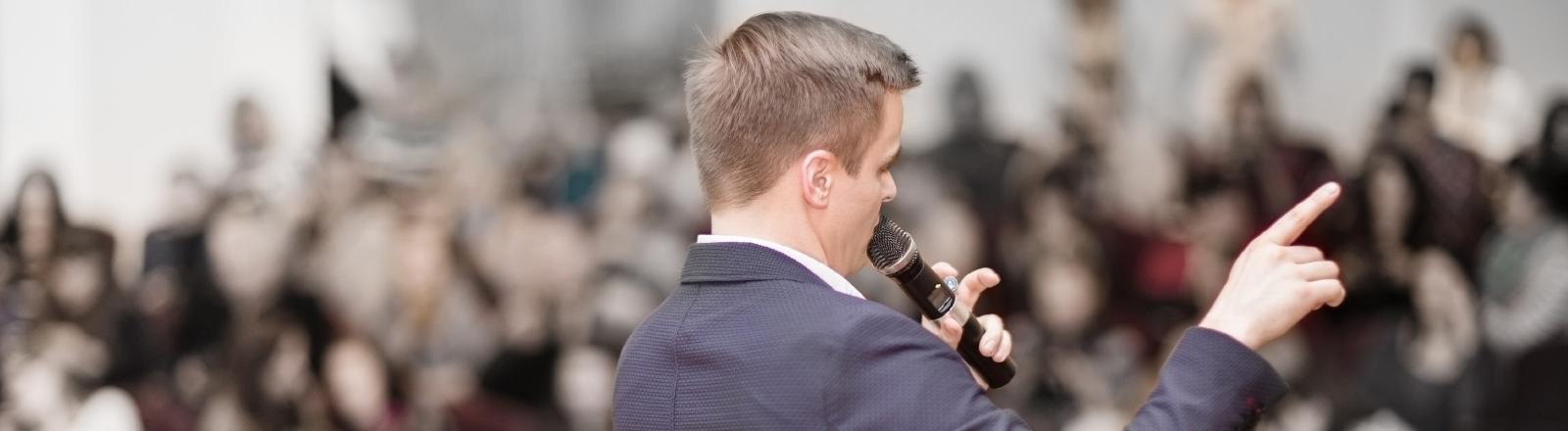 Ein Mann spricht ins Mikro vor eine großen Menschenmenge
