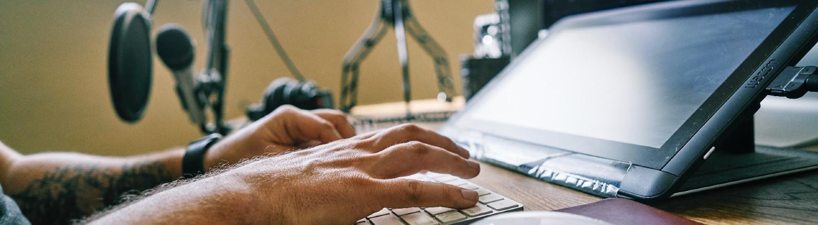 Mann sitzt am Computer am Schreibtisch.