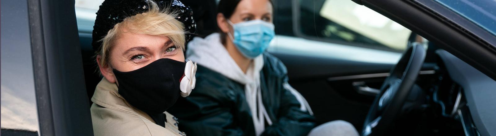 Zwei Frauen mit Schutzmaske im Auto