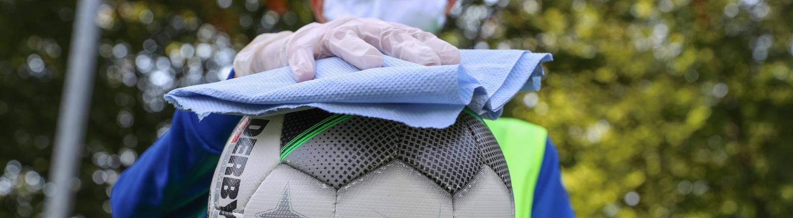 En Mann desinfiziert einen Fußball