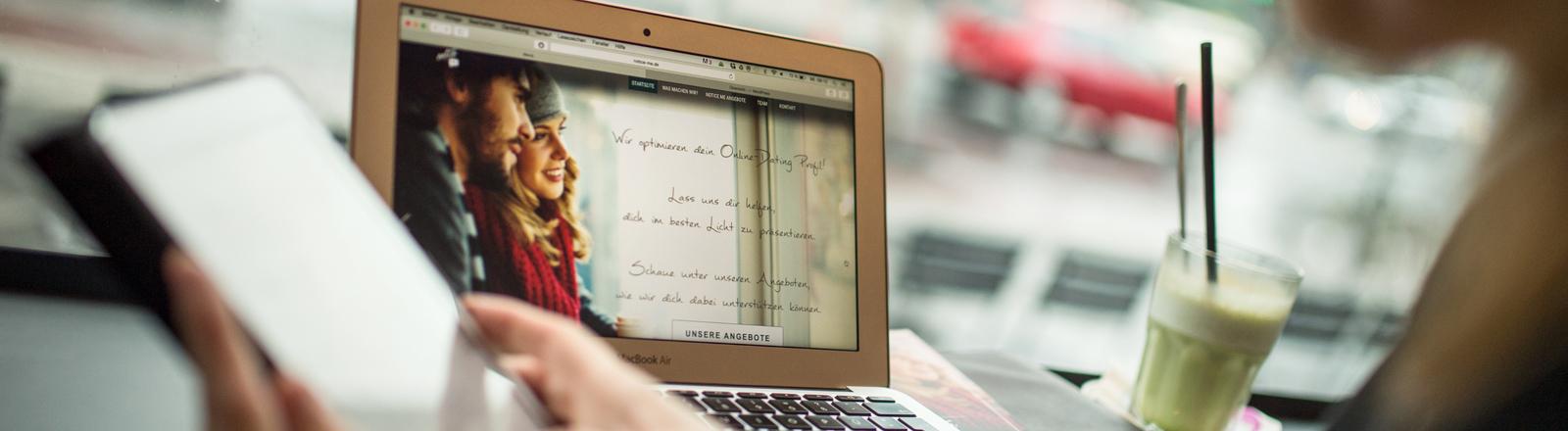 Zwei Hände halten ein iPad. Dahinter steht ein Laptop auf dem eine Dating-Seite zu sehen ist