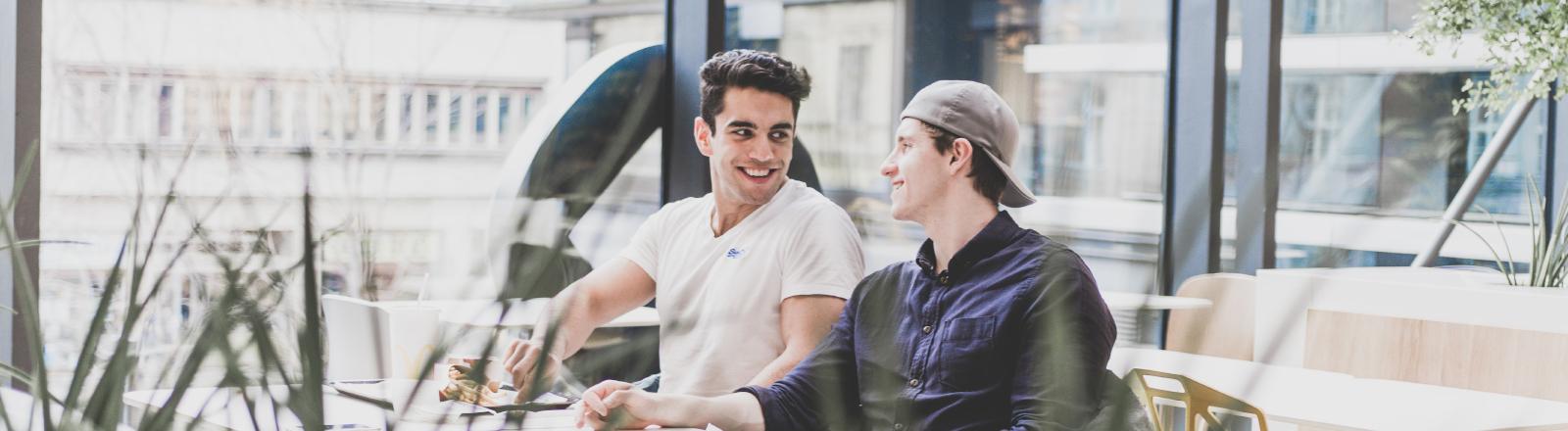 Zwei Männer sitzen nebeneinander und unterhalten sich in einem Café