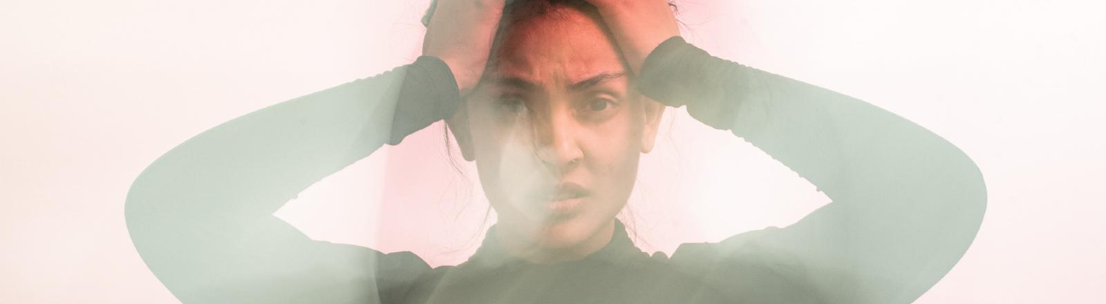 Eine junge Frau hält sich die Hände an den Kopf und blickt verzweifelt