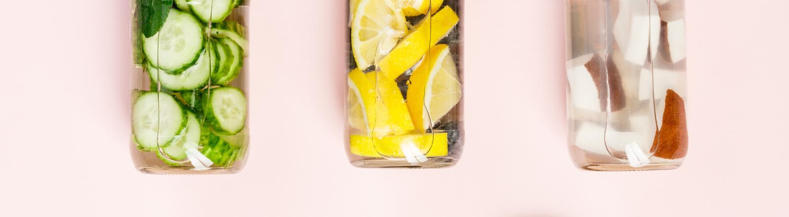 Flaschen mit Wasser und Früchten (Detox-Trend Fruit-Infusion)