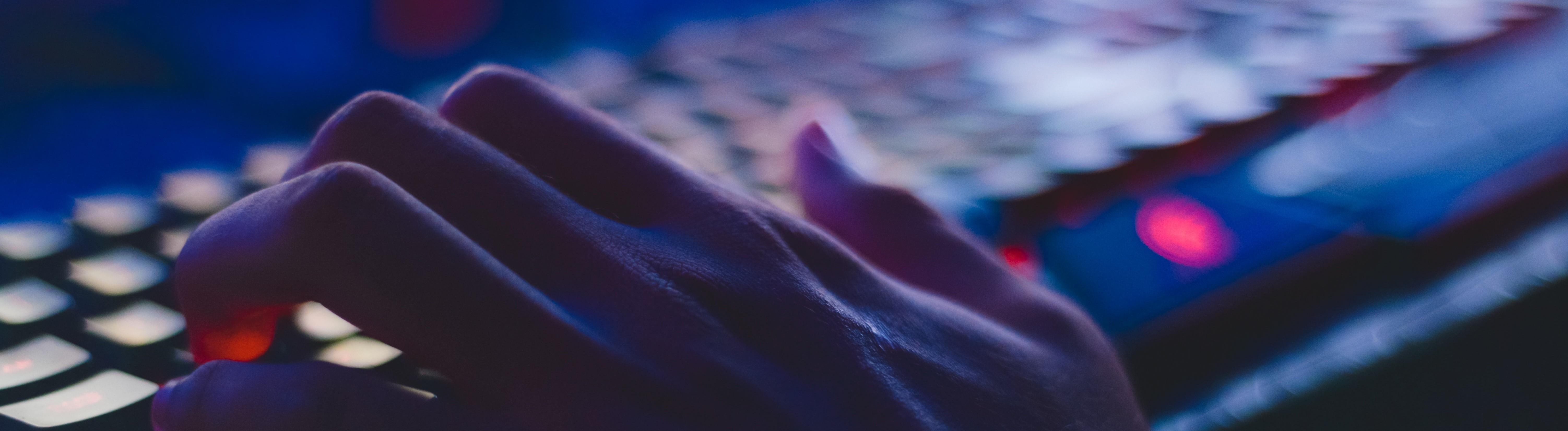 Eine Hand tippt auf einer beleuchteten Tastatur.