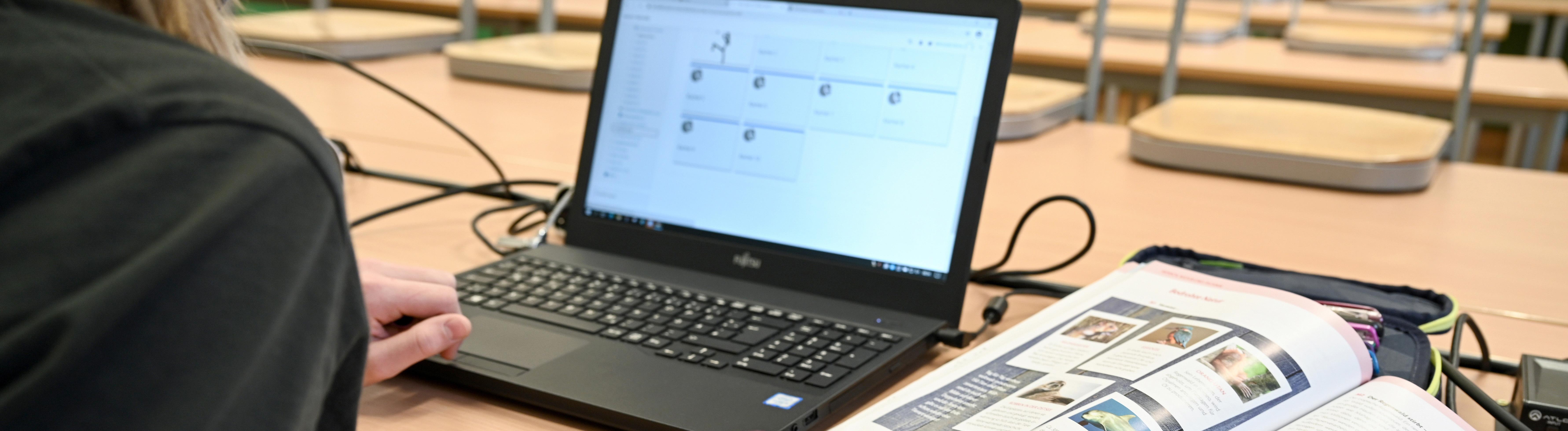 Schülerin mit Laptop in einem leeren Klassenzimmer