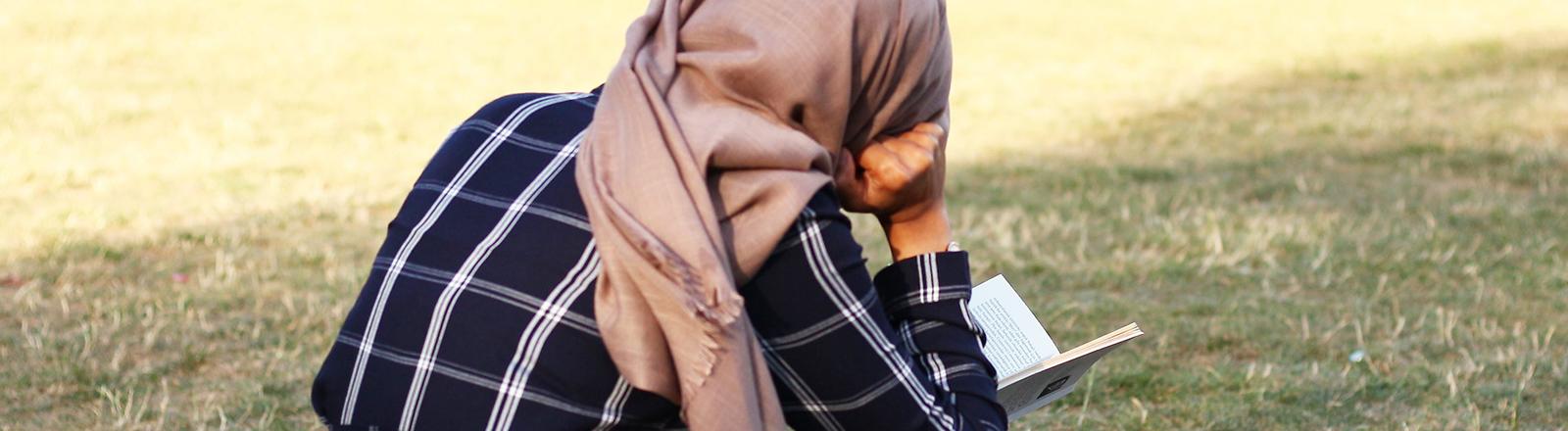 Junge Muslima sitzt in Berlin mit einem Buch auf der Wiese.