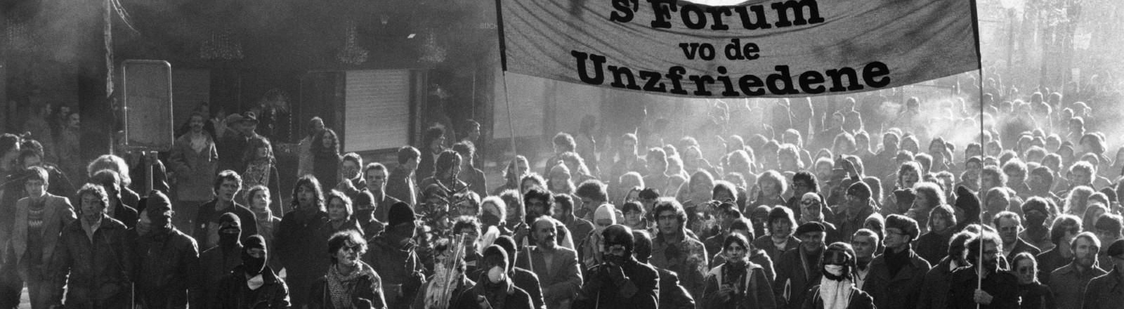 """Demonstration des """"Forums der Unzufriedenen"""" ('s Forum vo de Unzfriedene) auf der Bahnhofstraße im heissen Sommer 1980. Die Jugendunruhen in Zürich begannen am 30. Mai 1980 mit Protesten gegen die Subventionierung des Opernhauses, da Millionen für die etablierte, aber wenig für alternative Kultur ausgegeben werden."""