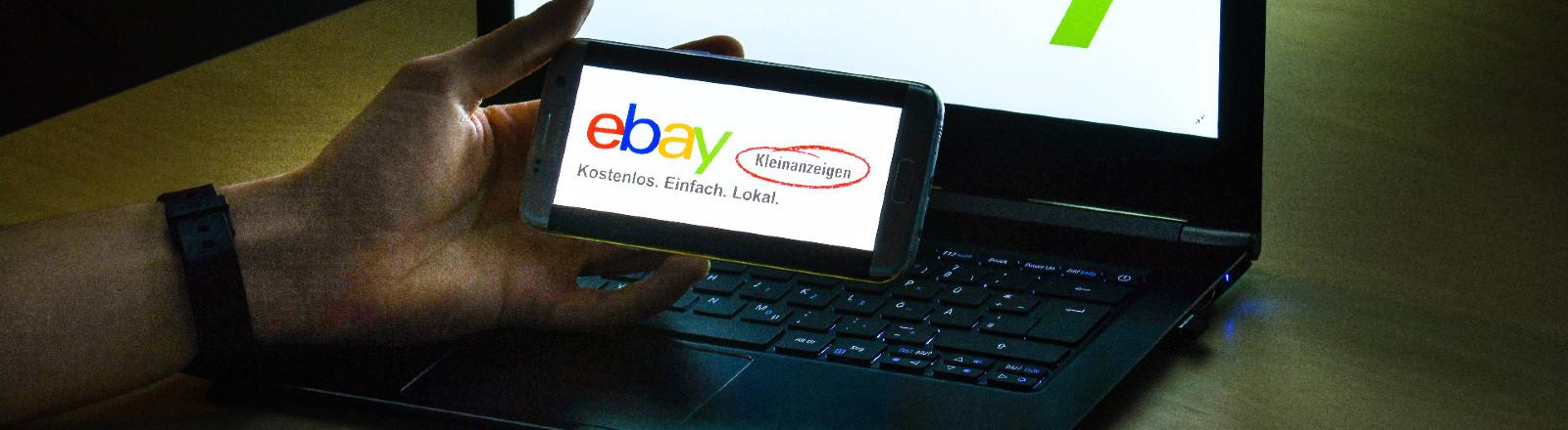 Mann hält Smartphone mit Logo von Ebay Kleinanzeigen vor einem Laptop mit ebay-Logo