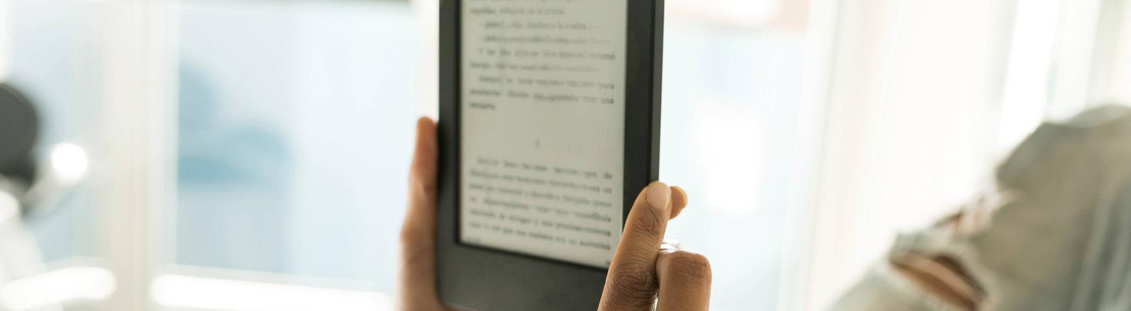 Eine Person liegt auf einem Bett und liest ein E-Book.
