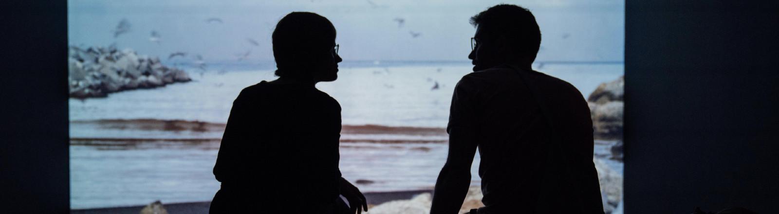 Paar sitzt vor einem Kunstwerk in einer Ausstellung.