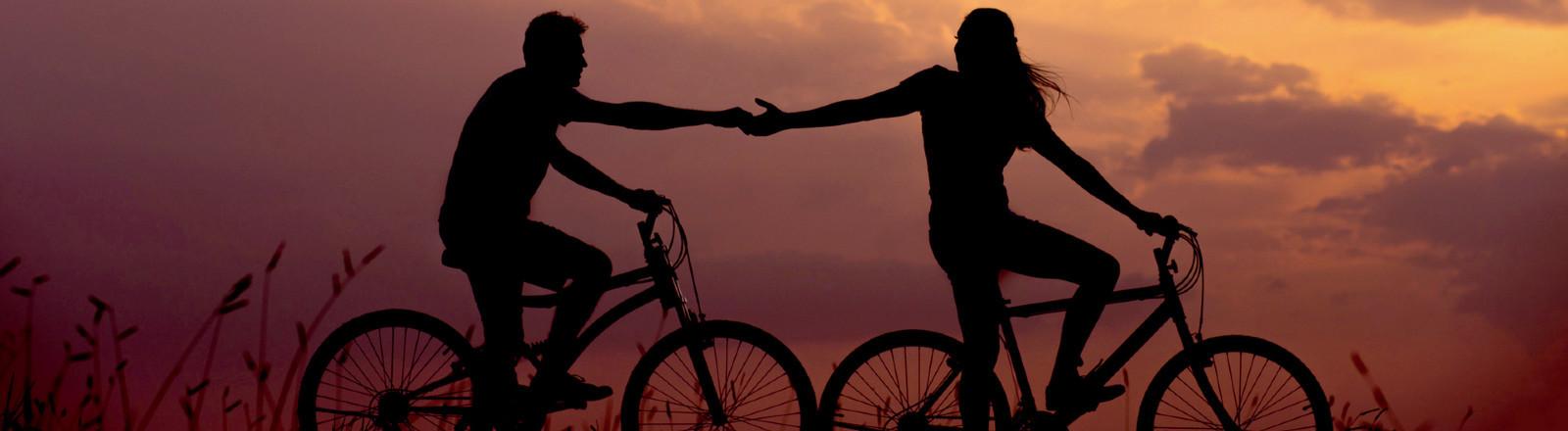 Paar fährt Rad vor Sonnenuntergang.
