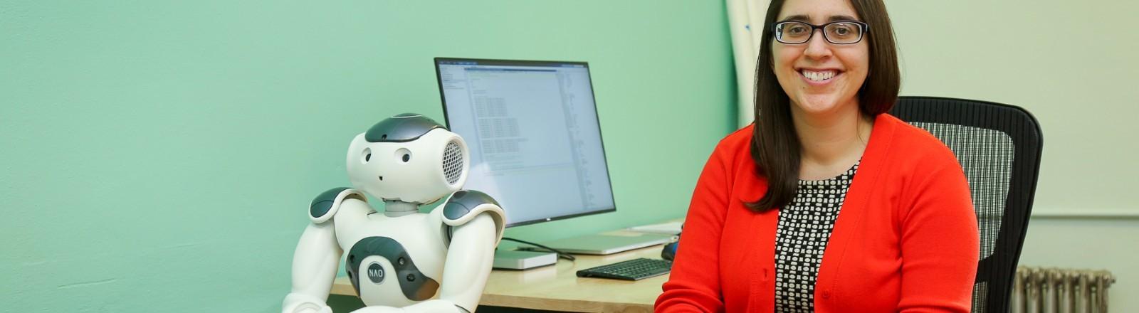 Naomi Fitter sitzt mit dem Roboter an einem Schreibtisch