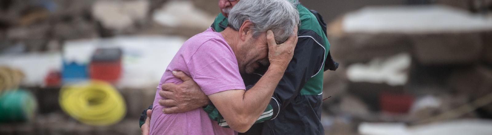 Zwei Brüder stehen vor ihrem zerstörten Haus und umarmen sich, 19.7.2021