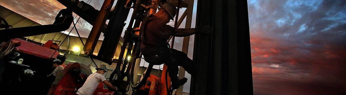 Mann arbeitet im Morgengrauen an einem Frackeng-Bohrturm in North Dakota