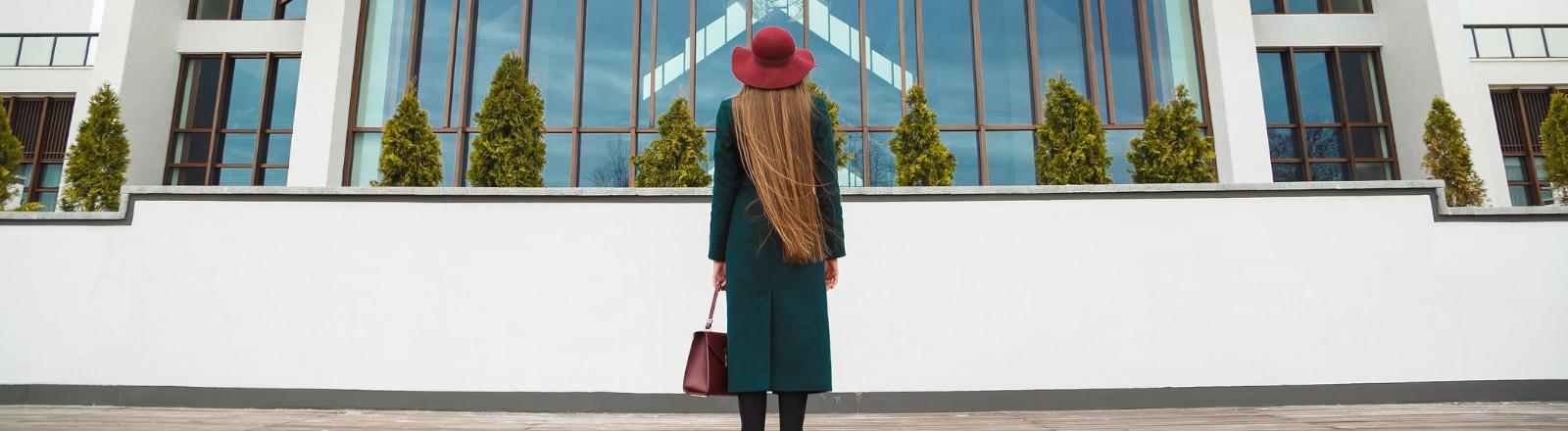 Eine Frau steht vor einem großen Haus