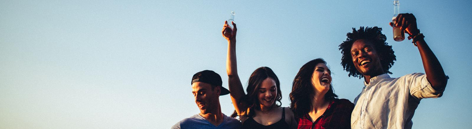 Vier jugendliche feiern vor blauem himmel