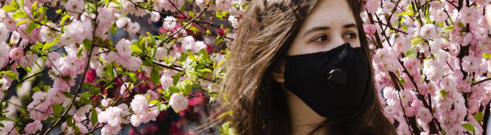 Frau mit Mundschutz steht vor blühenden Bäumen