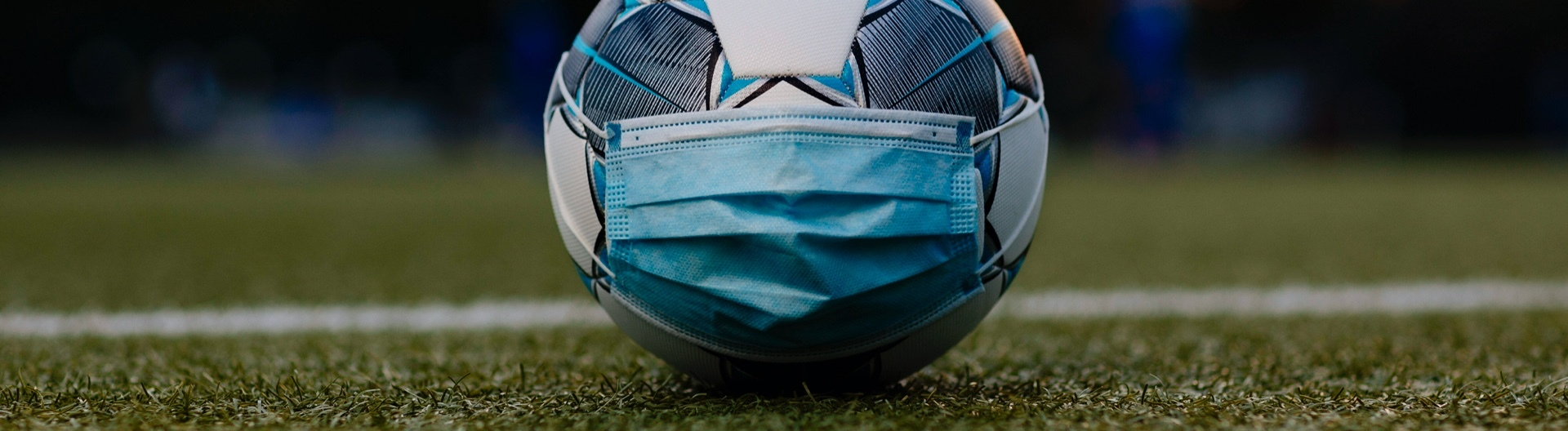 Fußball mit Mundschutz auf Fußballfeld