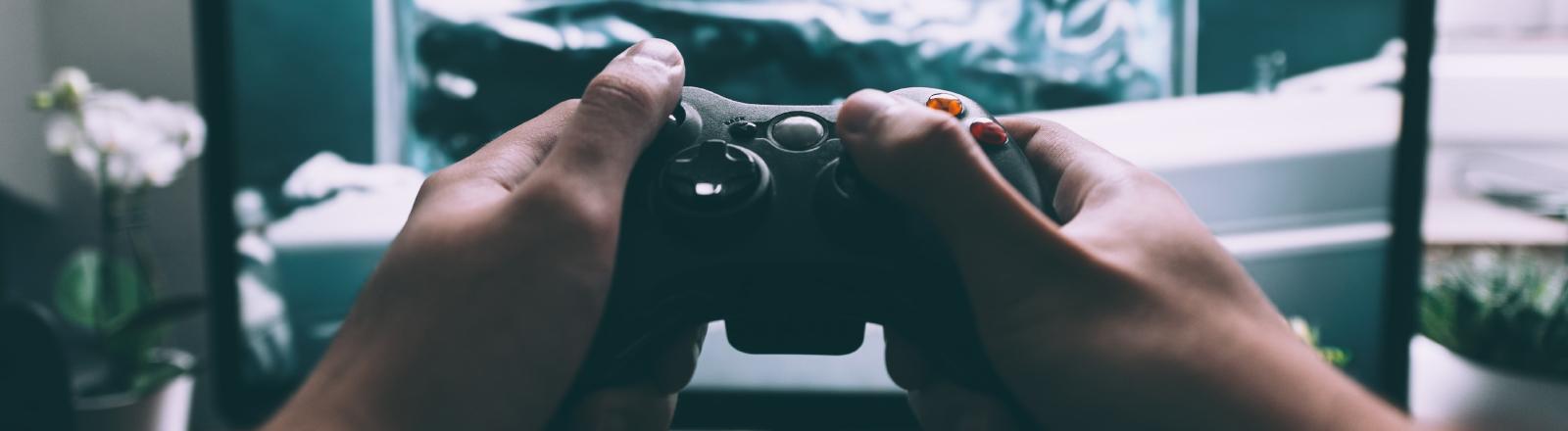 Ein Mann hält eine Gaming-Konsole