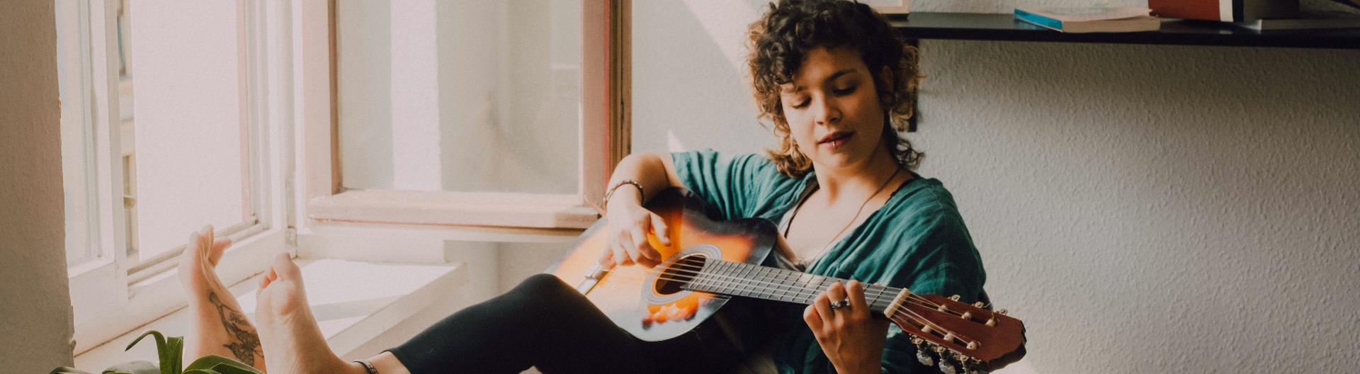 Junge Frau sitzt am Fenster und spielt Gitarre