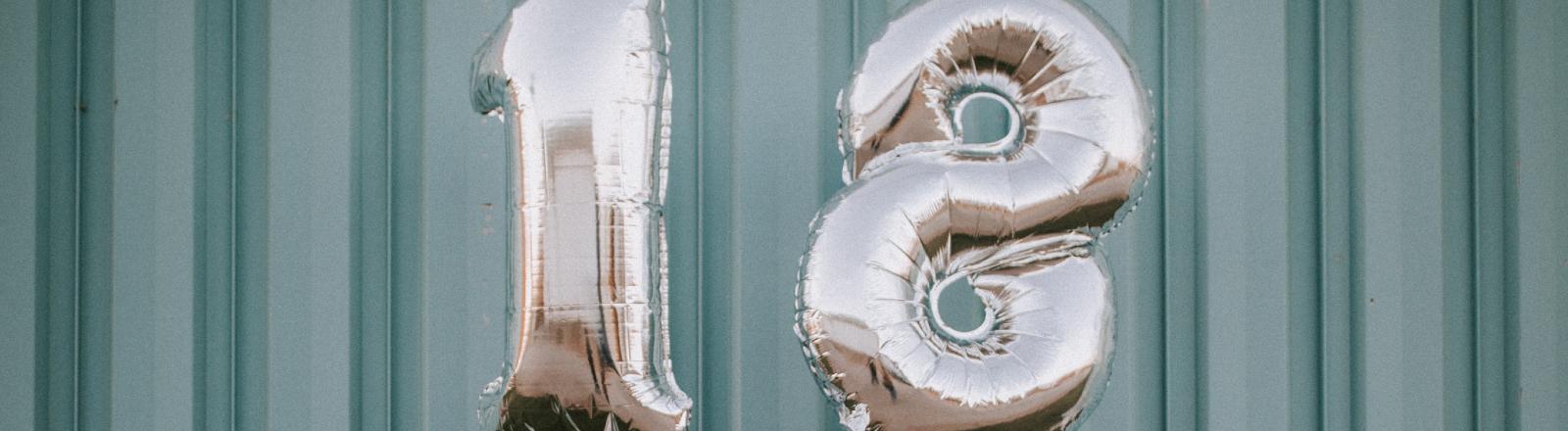 Frau hält silberne Geburtstags-Luftballons in den Händen.