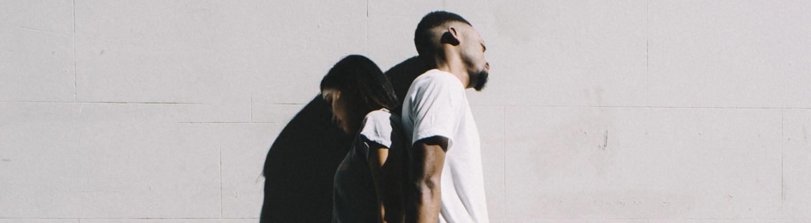 Junges Paar lehnt an einer Mauer