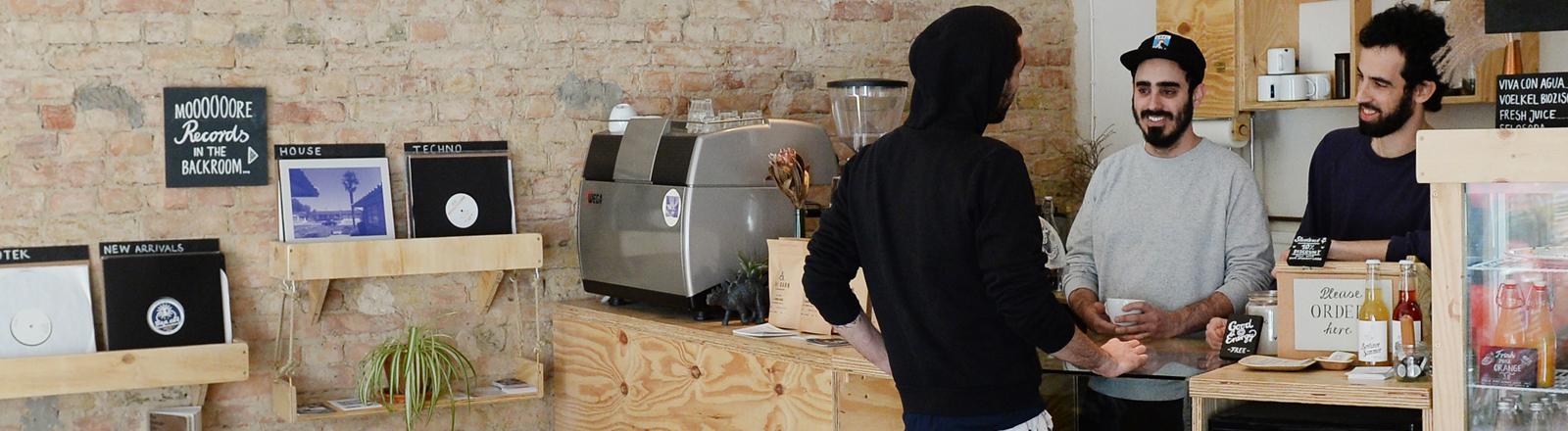 junge cafebetreiber mit einem kunden an der theke