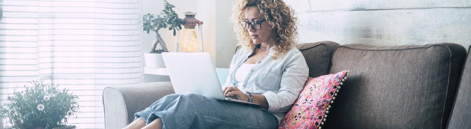 Frau sitzt mit Laptop auf Sofa