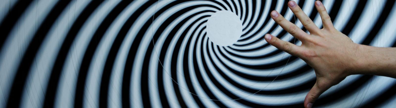 Eine Hand über einer Hypnose-Spirale