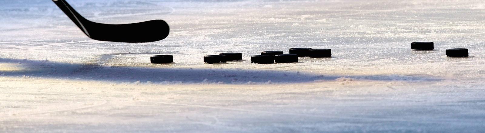 Eishockeyschläger und Pucks auf einem Eishockey-Spielfeld.