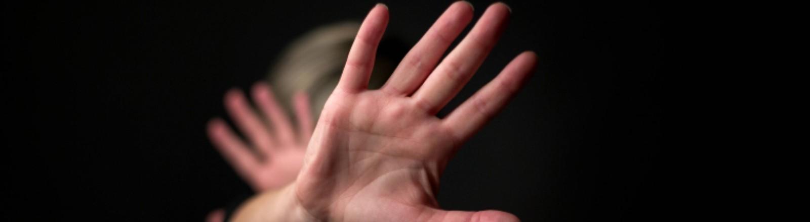 Eine Frau hält sich die Hände vors Gesicht, um sich zu schützen