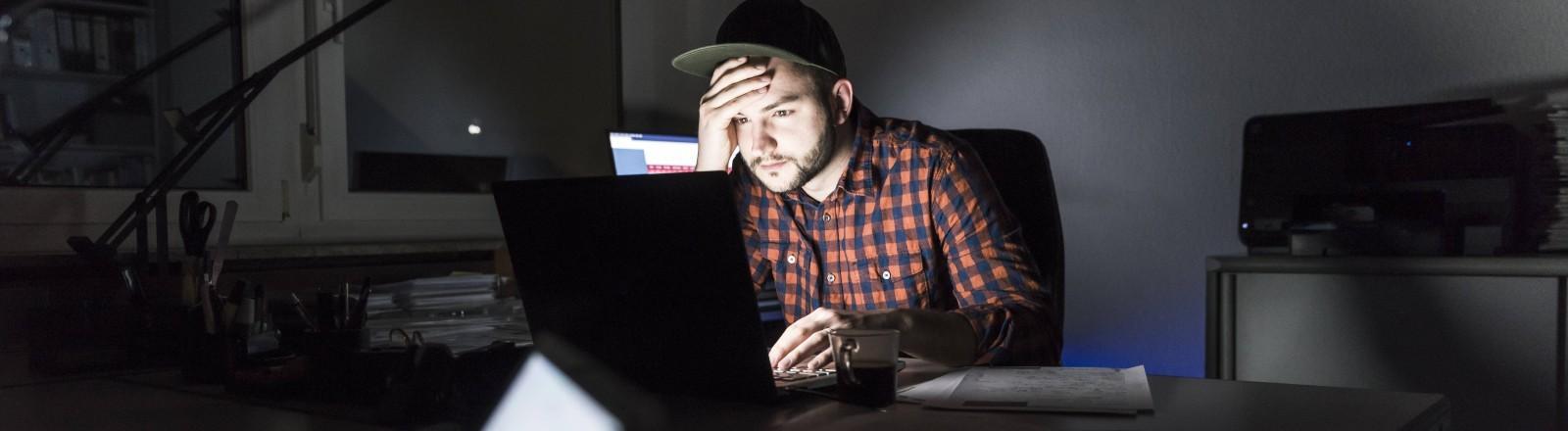 Ein Mann sitzt im Dunklen und schaut in einen hell leuchtenden Laptop