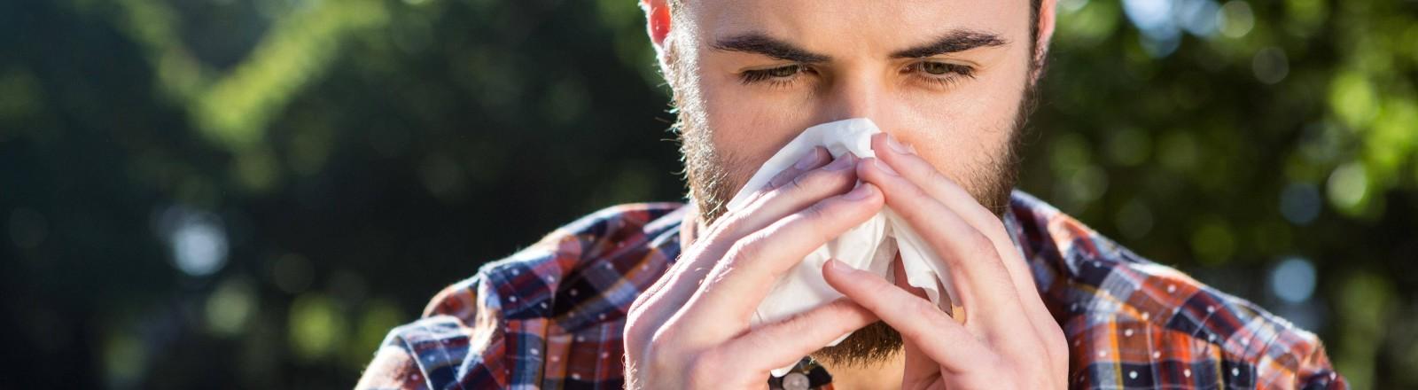 Ein Mann putzt sich die Nase in der Natur