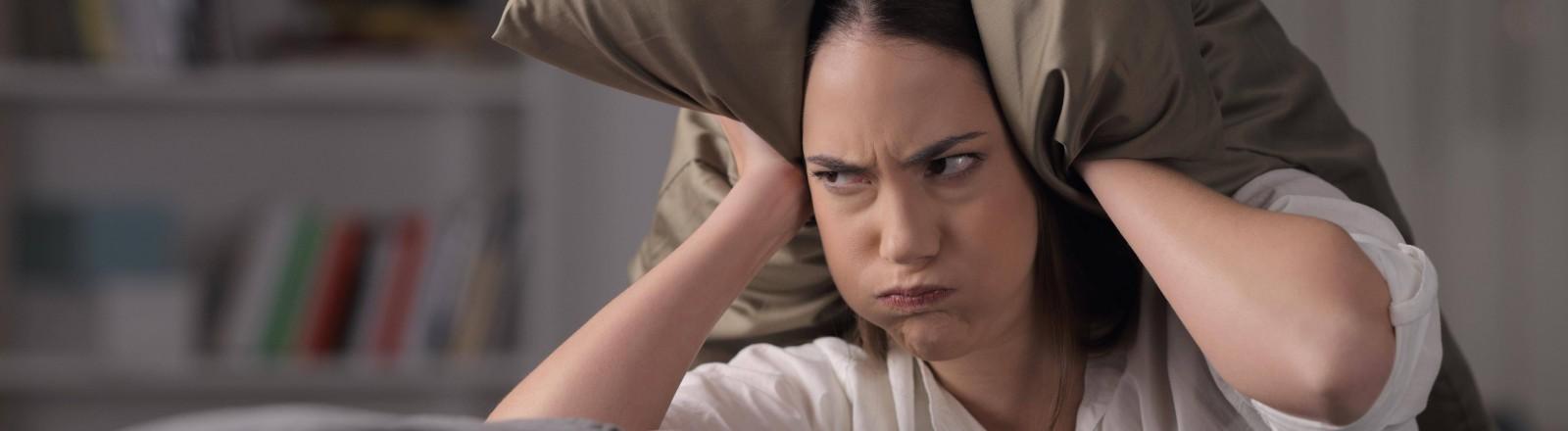 Eine Frau hält sich ihre Ohren mit einem Kissen zu