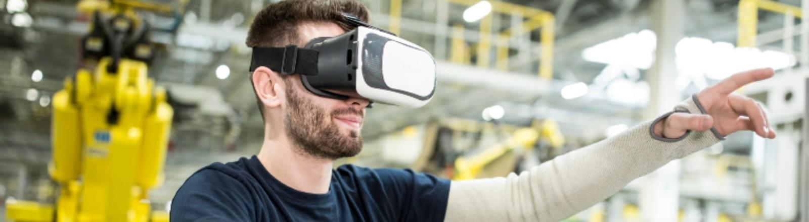 Ein Mann steht in einer Fabrik und hat eine VR-Brille auf