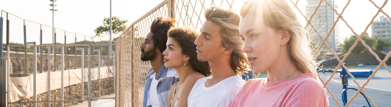 Vier junge Menschen lehnen an einen Zaun