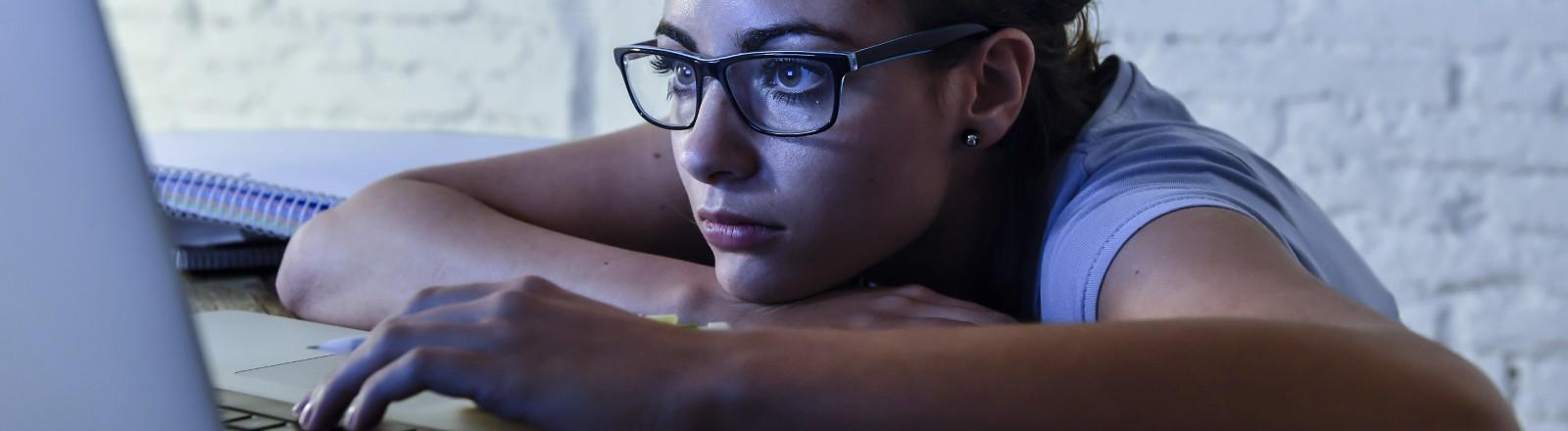 Eine junge Frau schaut genervt in ihren Bildschirm
