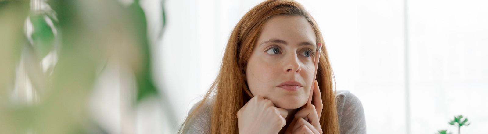 Eine junge Frau sitzt im Zimmer und denkt nach