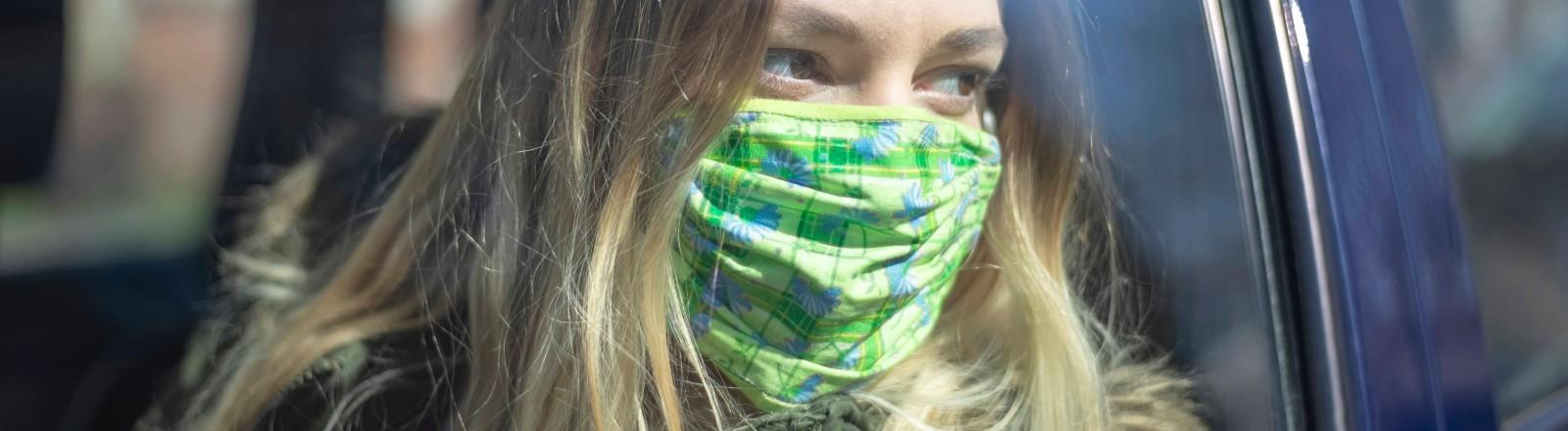Junge Frau mit Maske im Auto