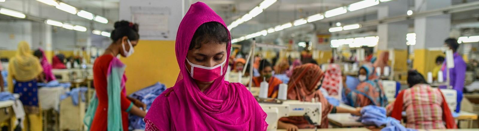 Eine Näherin in Bangladesch mit Schutzmaske