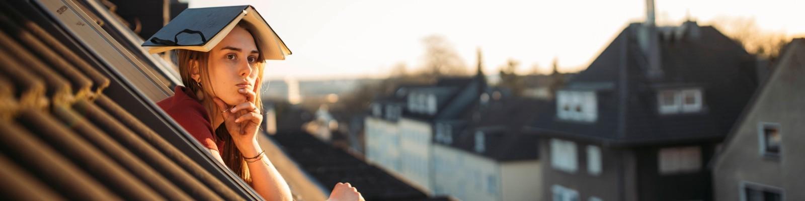 Eine Frau mit einem Buch aus dem Kopf schaut denkend aus dem Fenster