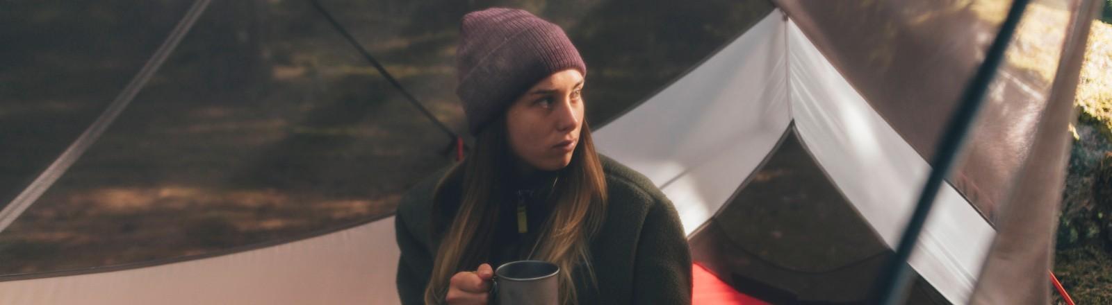 Ein Mädchen sitzt in einem Zelt alleine