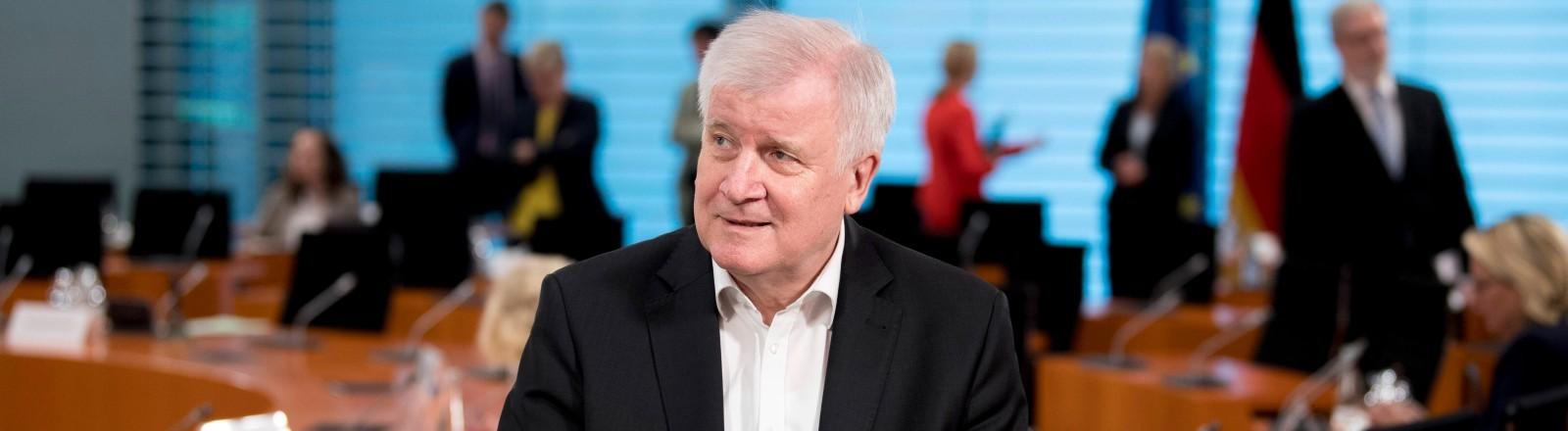 Horst Seehofer sitzt angelehnt an einen Tisch in einem Konferenzraum