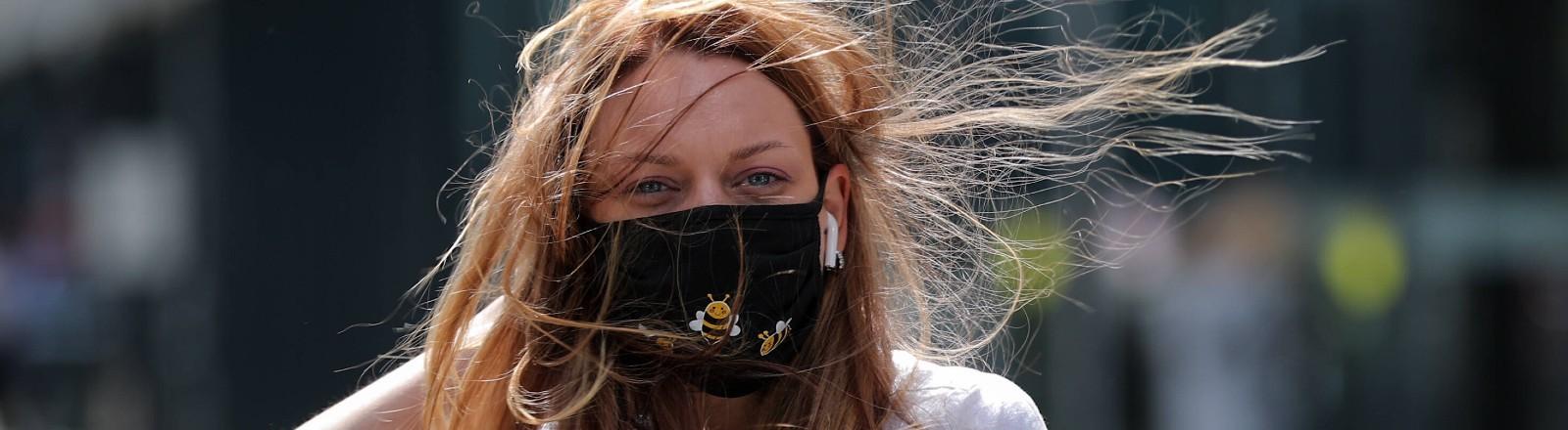 Eine Frau mit Maske und wehendem Haar